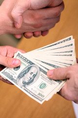 Businessman setting a deal passing money and shaking hands
