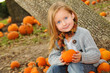 Little Blonde Girl holding a Pumpkin in Pumpkin Patch