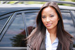 Young beautiful asian businesswoman against luxury car