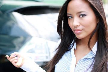 Young attractive asian businesswoman closes the door of her car