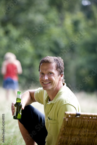 A middle aged man sitting on the grass