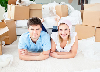 Smiling couple lying on the floor after unpacking boxes