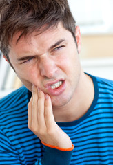 Unhappy caucasian man having a toothache in the living-room
