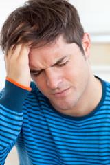 Cute man having a headache in the living-room