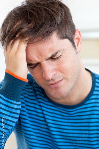 Cute man having a headache in the living-room