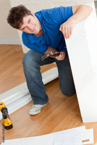 Smiling man assembling furniture and holding a hammer
