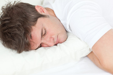 Young caucasian man sleeping in his bed