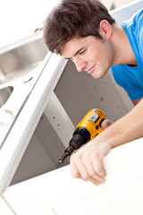 Confident man holding a drill repairing a kitchen sink