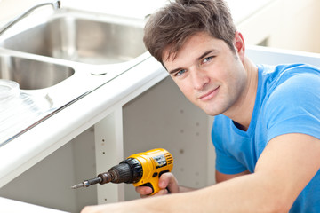 Handsome man holding a drill repairing a kitchen sink