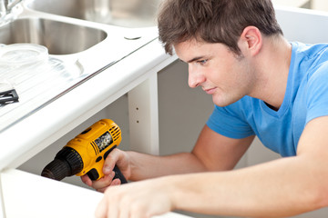 Self-assured man holding a drill repairing a kitchen sink