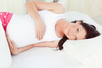 Young pregnant woman resting in her bed in the bedroom