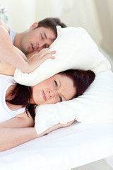 Young woman annoyed by the snores of her boyfriend in the bedroo