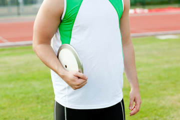 Close-up of a male athlete holding a discus