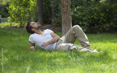 jeune homme couché dans l'herbe détente