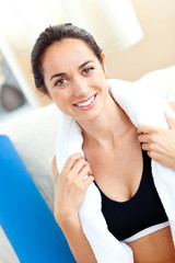 Smiling athletic hispanic woman with a towel sitting on the sofa