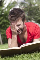 jeune homme riant lisant un livre délassement