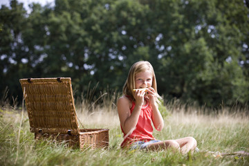 A young girl sitting on the grass, eating melon