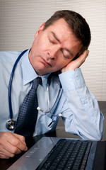 Tired doctor sleeps at desk