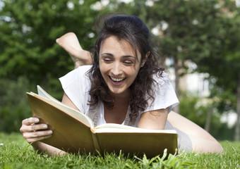 jeune fille riant en lisant un livre