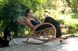 Fototapety Donna legge su sedia a dondolo  in giardino