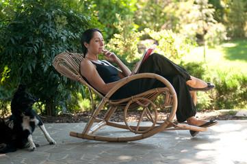 Donna legge su sedia a dondolo  in giardino