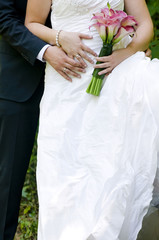 Bride and groom showing wedding ring and bouquet