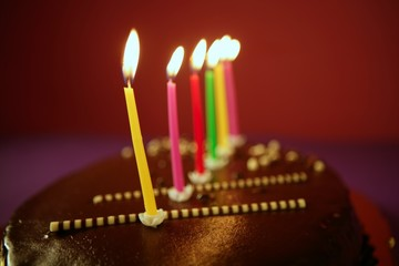 Colorful birthday light candles in chocolate cake