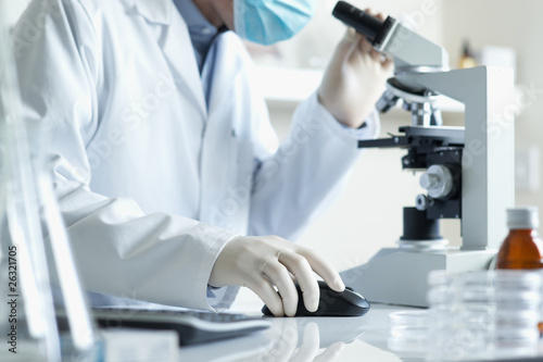 Scientist with  microscope and computer
