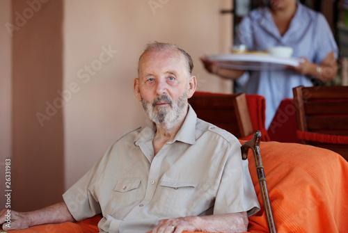 senior elderly man with carer serving meal