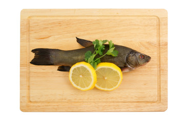 Raw tench with lemon and parsley on cutting board isolated