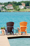 brown and orange adirondack chairs on a dock