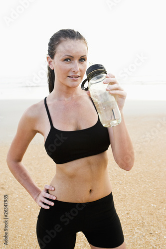 Healthy fit young woman on beach drinking water