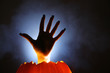 Human hand raising from glowing pumpkin Jack-o-lantern