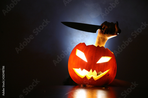 Hand with knife raising from glowing pumpkin lantern