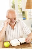 Laughing pensioner reading book poster