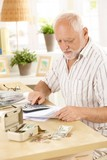 Active pensioner doing financial work at home poster