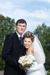 smiling bride with groom outdoors against trees and blue sky