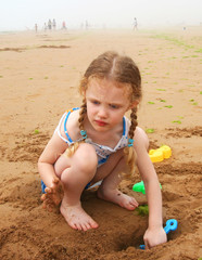 A Little Girl Digging at the Beach with a Blue Shovel