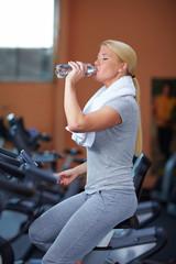 Frau trinkt Wasser im Fitnesscenter