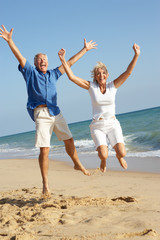 Senior Couple Enjoying Beach Holiday Jumping In Air
