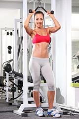 Full length portrait of a woman working out on a fitness equipme