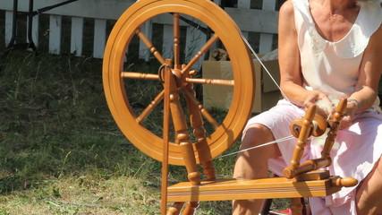 Woman spins yarn on old loom