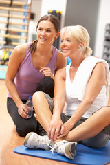 Woman Doing Stretching Exercises In Gym With Trainer