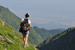 single woman with backpack walking on mountains