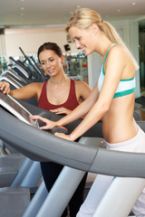 Woman Working With Female Personal Trainer On Running Machine In