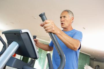 Senior Man On Cross Trainer In Gym