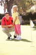 Father Teaching Daughter To Play Golf On Putting On Green