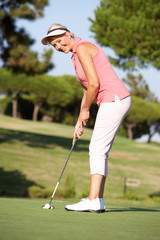 Senior Female Golfer On Golf Course Lining Up Putt On Green