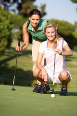 Two Female Golfers On Golf Course Lining Up Putt On Green