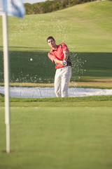 Male Golfer Playing Bunker Shot On Golf Course